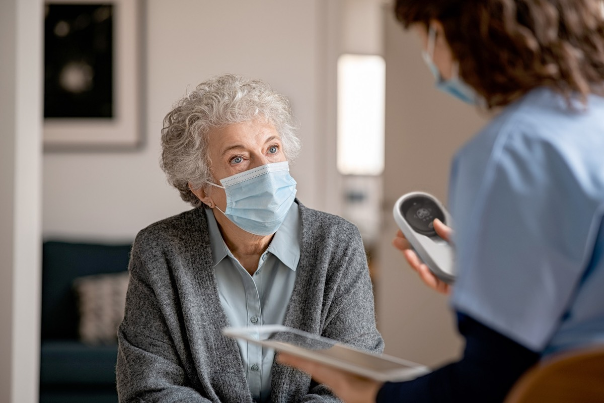 care taker with iPad talking to inhabitant in nursing home.